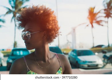 Young black pretty attractive female with curly hair looking around, walking on street of tropical city with palm trees and parked cars, sunny bright summer day, vintage color filter