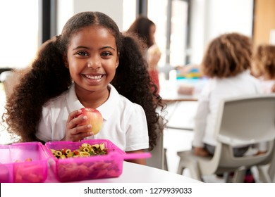 Young black schoolgirl sitting at a table smiling and holding an apple in a kindergarten classroom during her lunch break, close up