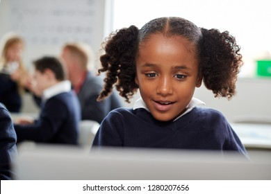 Young black schoolgirl using a laptop computer sitting at desk in a primary school classroom, front view, close up