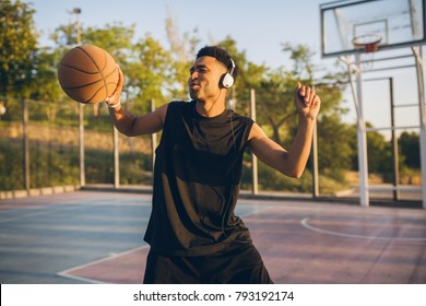 young black smiling man playing basketball on court on sunrise, morning sports, listening to music on headphones, funny face expression, emotional, positive energy, having fun