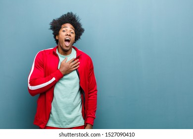 young black sports man feeling shocked, astonished and surprised, with hand on chest and open mouth, saying who, me? against grunge wall