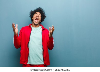 young black sports man furiously screaming, feeling stressed and annoyed with hands up in the air saying why me against grunge wall