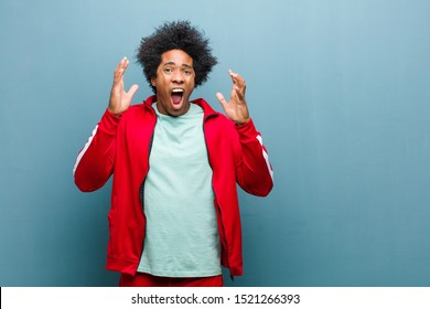 young black sports man screaming with hands up in the air, feeling furious, frustrated, stressed and upset against grunge wall