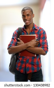 Young Black Student holding a copybook isolated on a white background