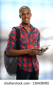Young black student holding an electronic tablet isolated on a white background