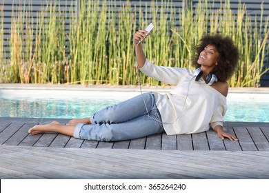 young black student laying out near the pool and taking a selfie.