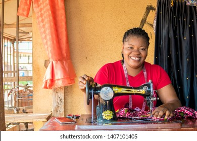 young black tailor smiling while she's working