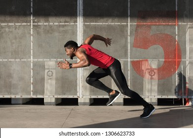 Young black urban athlete running and sprinting.