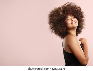 young black woman with afro hair. pink background