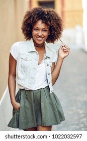 Young black woman, afro hairstyle, smiling in the street. Girl wearing casual clothes in urban background. Female with skirt and denim vest