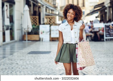Young black woman, afro hairstyle, with shopping bags in the street. Girl wearing casual clothes in urban background. Female with skirt, denim vest and high heels.