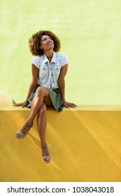 Young black woman, afro hairstyle, sitting on a wall smiling. Girl, model of fashion, wearing casual clothes in urban background. Female with skirt, denim vest and high heels.