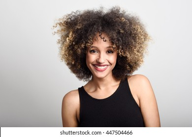 Young black woman with afro hairstyle smiling. Girl wearing black dress. Studio shot.