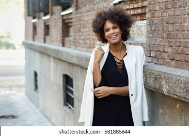 Young black woman with afro hairstyle smiling in urban background. Mixed  girl wearing white jacket 755ba82ab