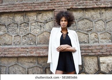 Young black woman with afro hairstyle standing in urban background. Mixed girl wearing white blazer jacket and black dress posing near a brick wall. Fashion model.