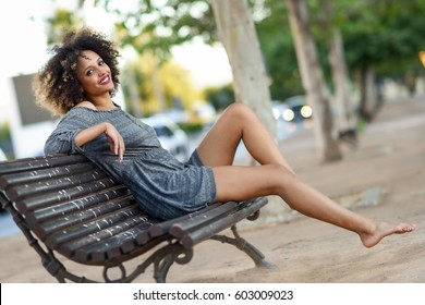 Young black woman with afro hairstyle sitting on a bench in urban  background moving her legs 67474672e