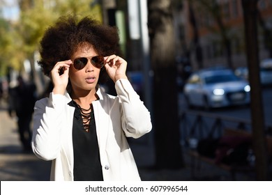 Young black woman with afro hairstyle standing in urban background with  aviator sunglasses. Mixed girl e289230f0