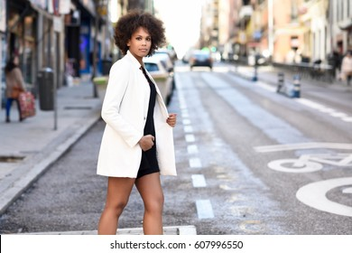 Young black woman with afro hairstyle walking on a crosswalk in an urban  street. Mixed 24defca74