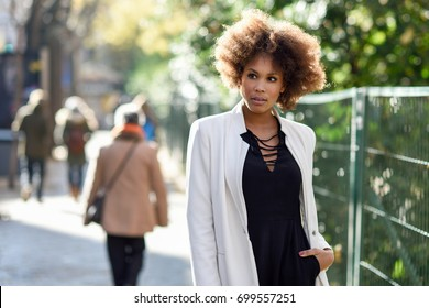 Young black woman with afro hairstyle standing in an urban street. Mixed  girl wearing white a0d02479d
