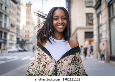 Young black woman in city flirting smiling to camera walking