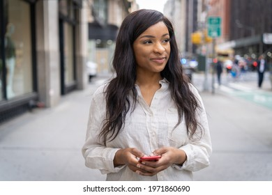 Young black woman in city walking street texting on cellphone