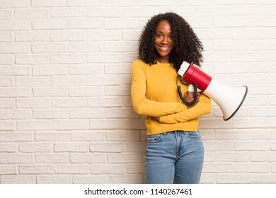 Young black woman crossing his arms, smiling and happy, being confident and friendly