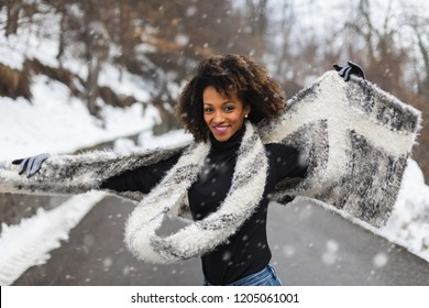 Young black woman dancing and having fun under the snow in cold winter.