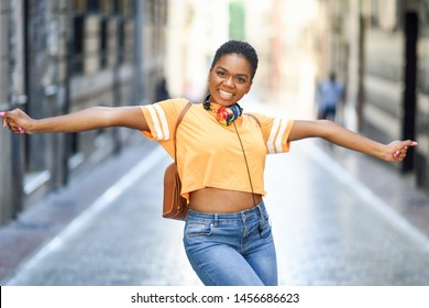 Young black woman is dancing on the street in Summer. Girl traveling alone. Lifestyle concept.