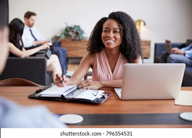 Young black woman at a desk looking to a colleague opposite