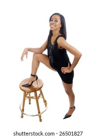 Young black woman in dress in bold stance leg on stool