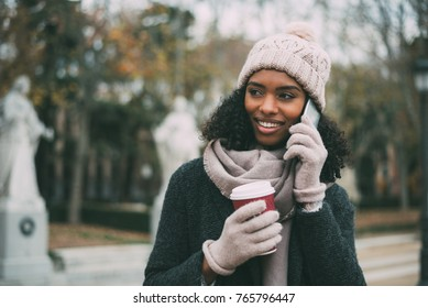 Young black woman drinking coffee and speaking on the mobile phone near the royal palace in winter