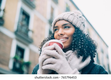 Young black woman drinking coffee wandering in the streets of Madrid on winter