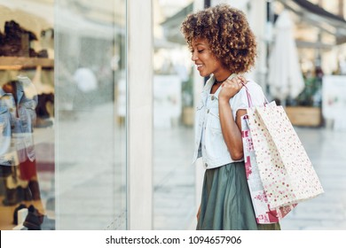 Young black woman in front of a shop window in a shopping street. African girl with afro hairstyle wearing casual clothes.