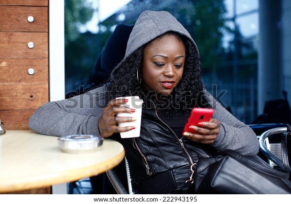 Young Black Woman in Gray Jacket with Hood Sitting on Chair Having Coffee While Busy Texting.