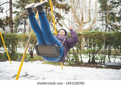 young black woman having fun on the swing outdoor in winter day – movement, enjoyment, youth