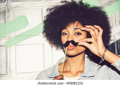 Young black woman having fun with a fake mustache
