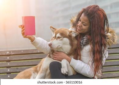 Young black woman and her dog (Siberian Husky) doing selfie