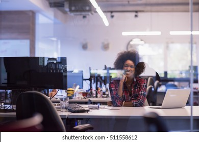 young black woman at her workplace in modern office  relaxing and working on laptop computer