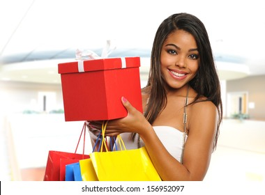 Young Black woman holding bags and a box inside a mall