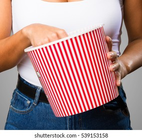 young black woman holding a popcorn bucket