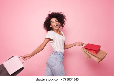Young black woman holding shopping bags on pink backgrond