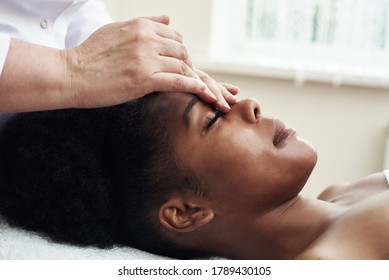 A young black woman lies in the beautician's office and relaxes from gentle touches and toning massage. The concept of spa treatments