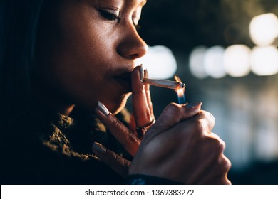 Young black woman lighting a joint