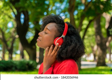 A young black woman listening to music on her headphones in a park.