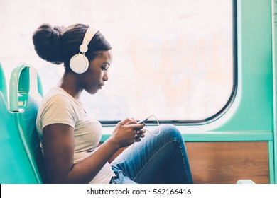 Young black woman listening music travelling by bus using smart phone hand hold, pensive - thoughtful, thinking future, music concept
