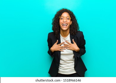 young black woman looking happy, surprised, proud and excited, pointing to self against blue wall