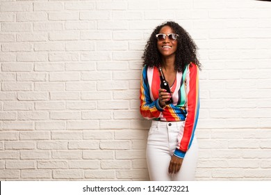 Young black woman looking up, thinking of something fun and having an idea, concept of imagination, happy and excited