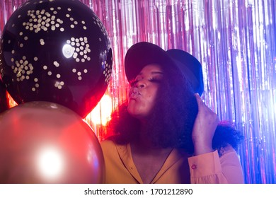 Young black woman looks happy while spend time in night club. Birthday party and nightlife concept.