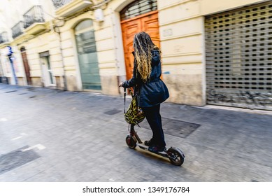 Young black woman moving on an electric scooter across the city.