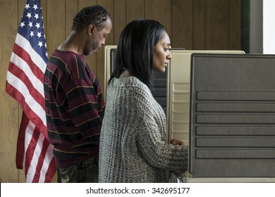 Young black woman and older black male voting in a booth